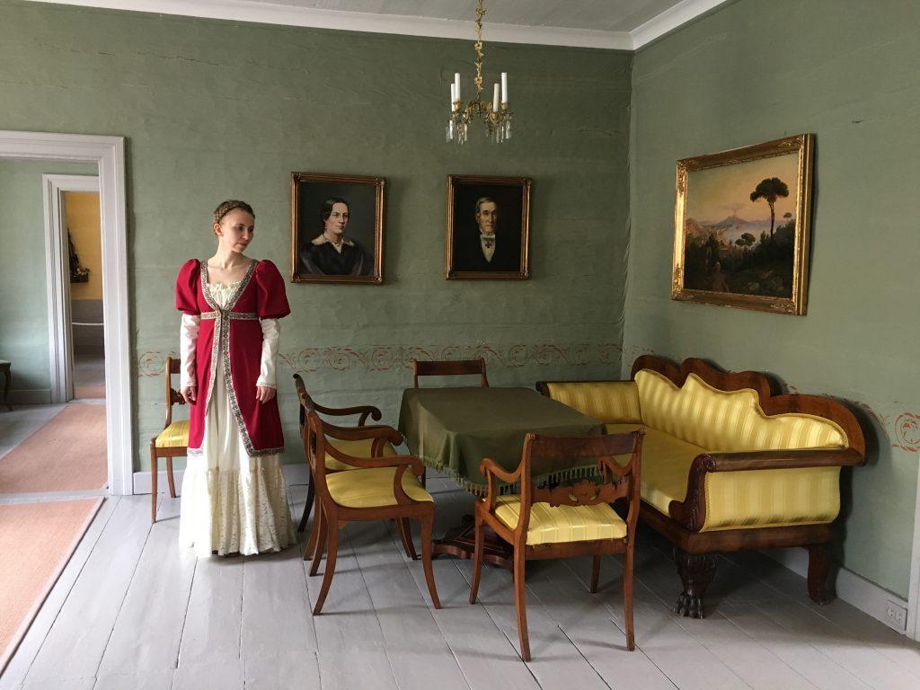 Kuvassa nainen historiallisessa asussa J. V. Snellmanin kotimuseossa. Vieressä keltainen sohvaryhmä ajan tyyliin ja seinällä maisemataulu, sekä muotokuvia.